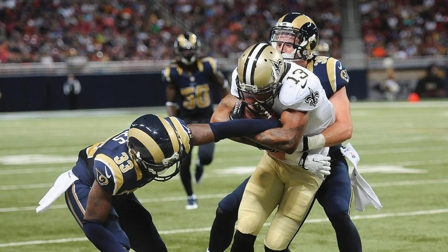 St. Louis Rams defenders E.J. Gaines (33) and Cody Davis, right, drag down New Orleans Saints wide receiver Joe Morgan (13) in the second quarter of a preseason NFL football game Friday, Aug. 8, 2014, in St. Louis. (AP Photo/L.G. Patterson)