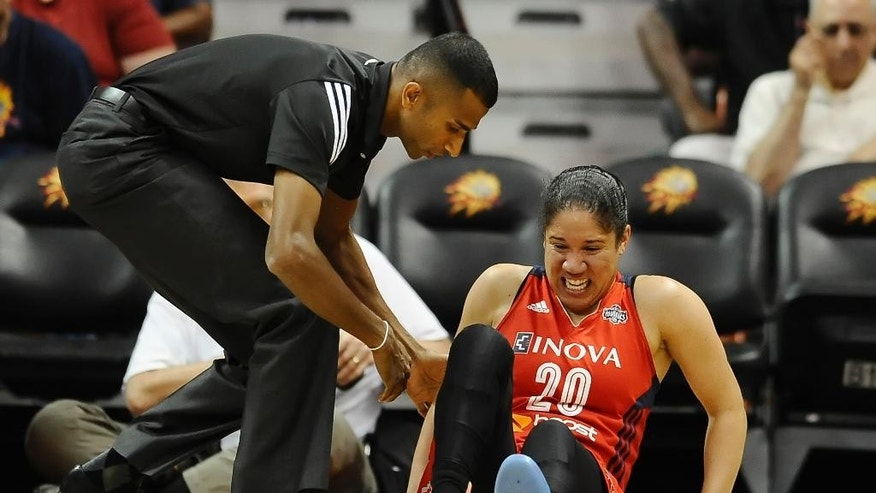Washington Mystics athletic trainer Navin Hettiarachch, left, comes to the aid of player Kara Lawson during the second half of a WNBA basketball game against the Connecticut Sun, Sunday, Aug. 10, 2014, in Uncasville, Conn. Lawson left the arena on crutches. (AP Photo/Jessica Hill)