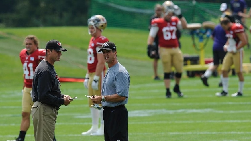 Baltimore Ravens head coach John Harbaugh, right, and San Francisco 49ers head coach Jim Harbaugh talk during a joint football practice, Saturday, Aug. 9, 2014, in Owings Mills, Md.(AP Photo/Gail Burton)