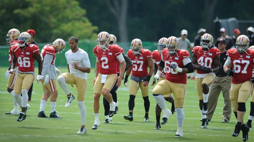San Francisco 49ers quarterback Colin Kaepernick, in white shirt, leads his team in drills in a joint football practice with the Baltimore Ravens , Saturday, Aug. 9, 2014, in Owings Mills, Md.(AP Photo/Gail Burton)