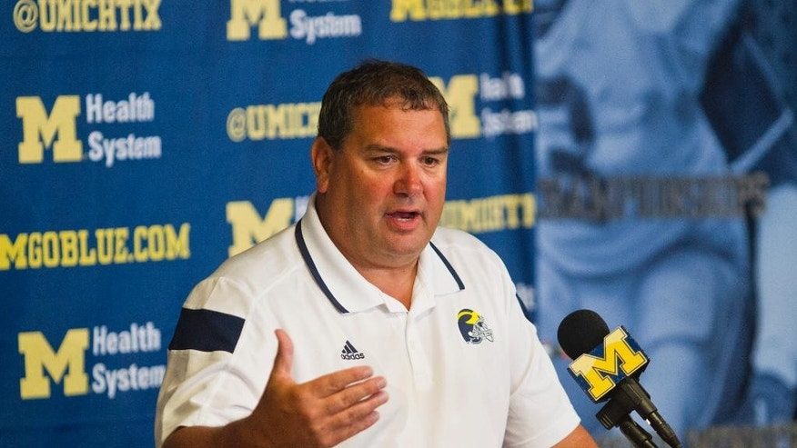 Michigan head coach Brady Hoke answers reporters' questions at a news conference during the NCAA college football team's preseason media day, Sunday, Aug. 10, 2014, in Ann Arbor, Mich. (AP Photo/Tony Ding)