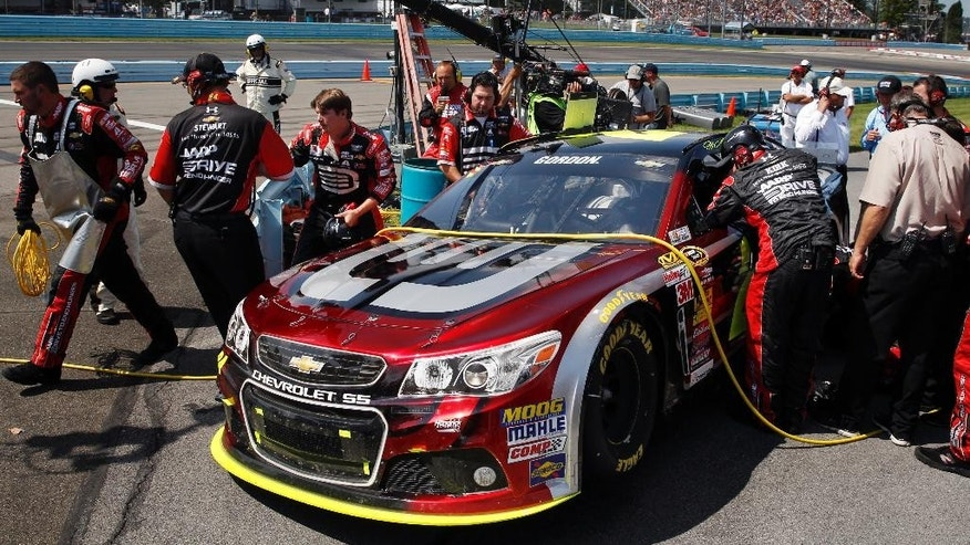 Crew members work on Jeff Gordon's car behind the pit wall during a NASCAR Sprint Cup Series auto race at Watkins Glen International, Sunday, Aug. 10, 2014, in Watkins Glen N.Y. (AP Photo/Mel Evans)