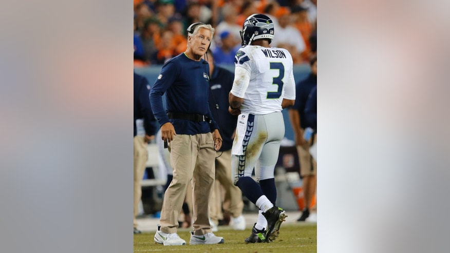 Seattle Seahawks coach Pete Carroll talks with quarterback Russell Wilson during the first half of an NFL preseason football game against the Denver Broncos, Thursday, Aug. 7, 2014, in Denver. (AP Photo/Jack Dempsey)