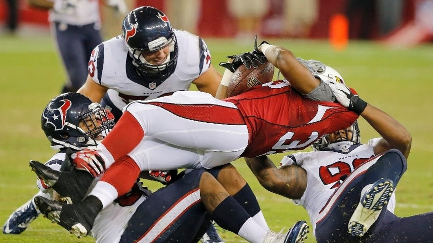 Arizona Cardinals running back Zach Bauman, center, is tackled by Houston Texans' Keith Browner, right, Max Bullough, rear, and Bronson Irwin, left, during the second half of an NFL preseason football game, Saturday, Aug. 9, 2014, in Glendale, Ariz. The Cardinals won 32-0. (AP Photo/Rick Scuteri)