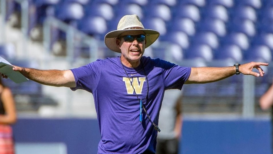 FILE - In this Aug. 4, 2014, file photo, Washington NCAA college football coach Chris Petersen gestures during practice at Husky Stadium in Seattle. The former head coach at Boise State, Petersen was finally persuaded by his gut. For years, Petersen was perfectly content. Yet something about Washington - the facilities, the setting, the conference, the history - all combined to finally give Petersen the feeling he needed to be challenged as a coach. So gone was the comfort of being at Boise State. And accepted was the task of escalating Washington's rise.(AP Photo/The News Tribune, Peter Haley, File) SEATTLE BROADCAST OUT