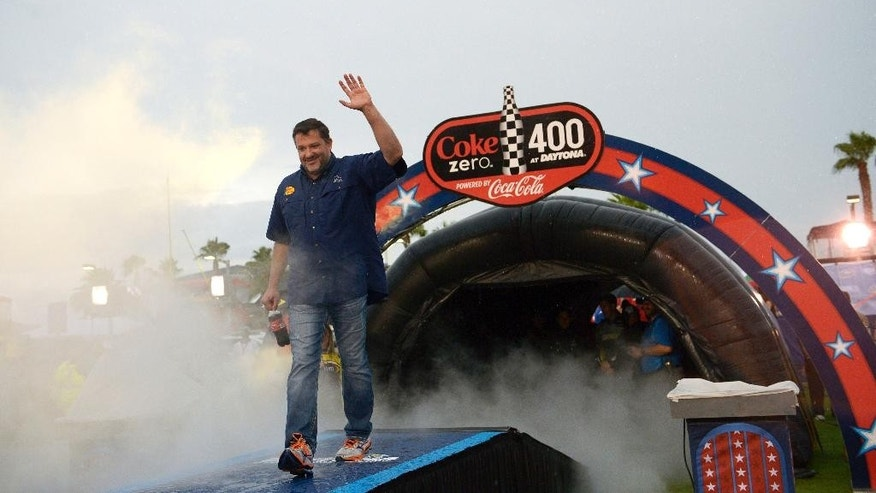 FILE - In this July 5, 2014, file photo, Tony Stewart walks down the runway during driver introductions before a NASCAR Sprint Cup Series auto race at the Daytona International Speedway in Daytona Beach, Fla. Racing sprint cars is Stewart's passion. But now his hobby, racing on tiny little tracks in nondescript towns outside of a busy NASCAR schedule, is again being called into question. The three-time NASCAR champion struck and killed a 20-year-old racer who had climbed from his car Saturday, Aug. 9, to confront Stewart on a New York dirt track following a crash caused by contact between the two cars. (AP Photo/Phelan M. Ebenhack, File)