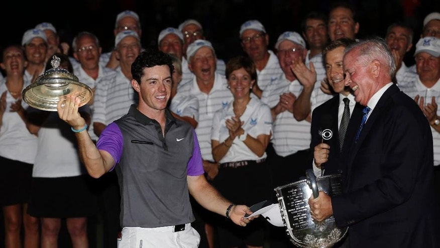 Rory McIlroy, of Northern Ireland, holds part of the Wanamaker Trophy after being presented the trophy from PGA of America president Ted Bishop after winning the PGA Championship golf tournament at Valhalla Golf Club on Sunday, Aug. 10, 2014, in Louisville, Ky. (AP Photo/David J. Phillip)