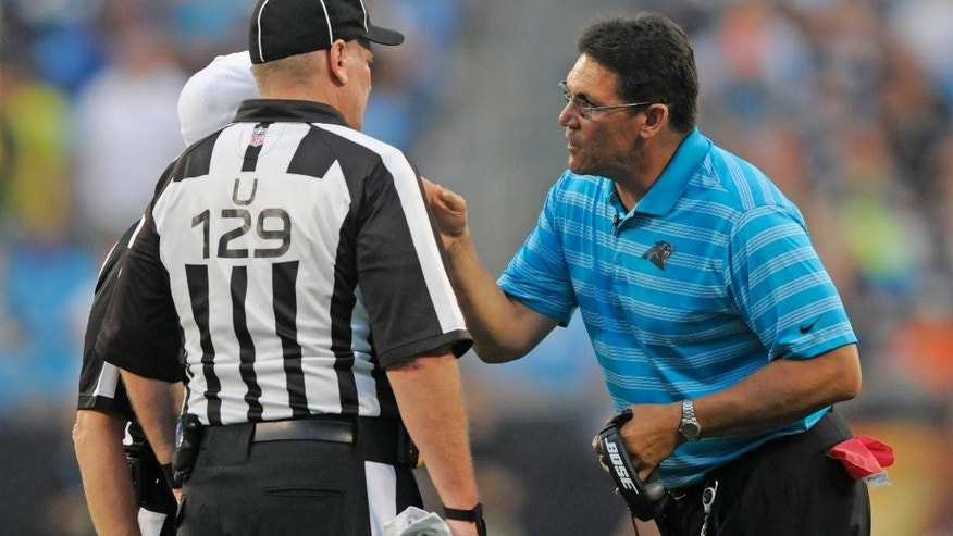 Carolina Panthers head coach Ron Rivera, right, argues a call with umpire Bill Schuster, left, during the first half of a preseason NFL football game in Charlotte, N.C., Friday, Aug. 8, 2014. (AP Photo/Mike McCarn)