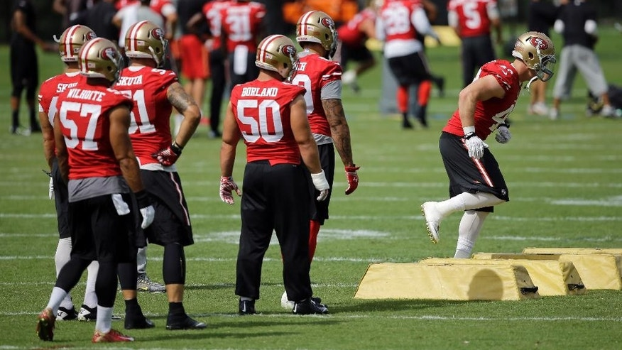 San Francisco 49ers linebacker Chase Thomas, right, runs a drill as teammates watch during an NFL football training camp practice, Monday, Aug. 11, 2014, in Owings Mills, Md. (AP Photo/Patrick Semansky)