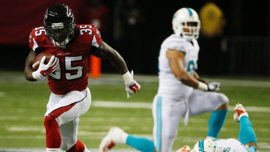 FILE - In this Aug. 8, 2014, file photo, Atlanta Falcons running back Antone Smith (35) moves past Miami Dolphins outside linebacker Koa Misi (55) during the first half of an NFL preseason football game in Atlanta. A player to watch may be running back Antone Smith, who showed promising big-play potential in the preseason opener, even though both his big gains were negated by penalties.   (AP Photo/John Bazemore, File)
