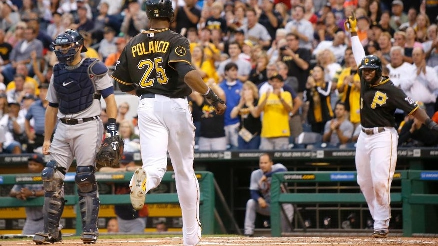 Pittsburgh Pirates' Gregory Polanco (25) heads home to score with Josh Harrison, right, and Ike Davis on a triple by Gregory Polanco in the first inning of the baseball game against the Detroit Tigers on Monday, Aug. 11, 2014, in Pittsburgh. Tigers catcher Alex Avila is at left. (AP Photo/Keith Srakocic)