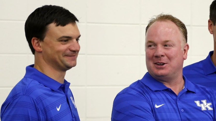 Kentucky head coach Mark Stoops, right and offensive coordinator Neal Brown share a laugh during the team's NCAA college football media day, Friday, Aug. 8, 2014, in Lexington, Ky. (AP Photo/James Crisp)