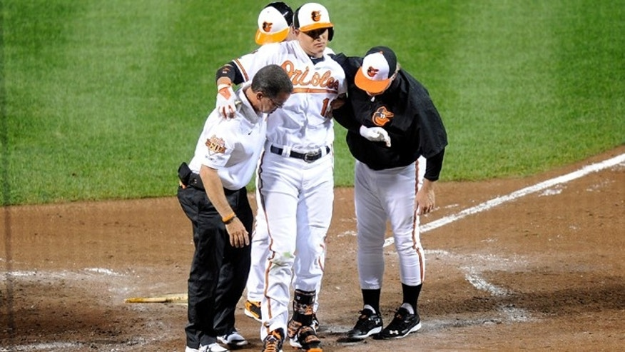 BALTIMORE, MD - AUGUST 11:  Manny Machado #13 of the Baltimore Orioles is helped off the field after injuring his leg in the third inning against the New York Yankees at Oriole Park at Camden Yards on August 11, 2014 in Baltimore, Maryland.  (Photo by Greg Fiume/Getty Images)