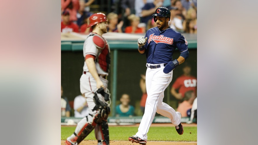 Cleveland Indians' Chris Dickerson, right, scores on an RBI-double by Indians' Jason Kipnis in the third inning of a baseball game, Tuesday, Aug. 12, 2014, in Cleveland. Diamondbacks catcher Miguel Montero watches. (AP Photo/Tony Dejak)