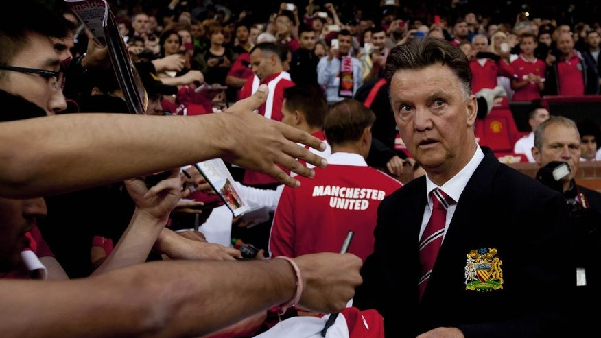 Manchester United's new manager Louis van Gaal, right, signs autographs as he takes to the touchline before his team's pre season friendly soccer match against Valencia at Old Trafford Stadium, Manchester, England, Tuesday Aug. 12, 2014. (AP Photo/Jon Super)