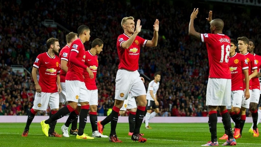 Manchester United's Darren Fletcher, centre, celebrates with teammates after scoring against Valencia, during a pre season friendly soccer match at Old Trafford Stadium, Manchester, England, Tuesday Aug. 12, 2014. (AP Photo/Jon Super)