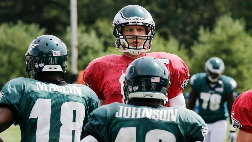Philadelphia Eagles quarterback Nick Foles talks with teammates during an NFL football training camp scrimmage of the New England Patriots and Eagles in Foxborough, Mass., Tuesday, Aug. 12, 2014. (AP Photo/Charles Krupa)