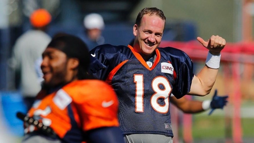 Denver Broncos' Peyton Manning smiles while stretching during NFL football training camp on Tuesday, Aug 12, 2014, in Englewood, Colo. (AP Photo/Jack Dempsey)