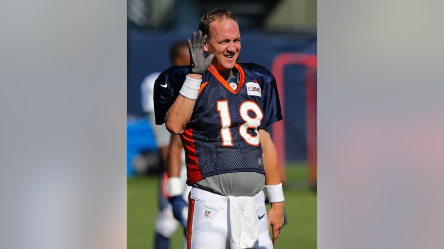 Denver Broncos' Peyton Manning holds up his gloved throwing hand during NFL football training camp on Tuesday, Aug 12, 2014, in Englewood, Colo. (AP Photo/Jack Dempsey)