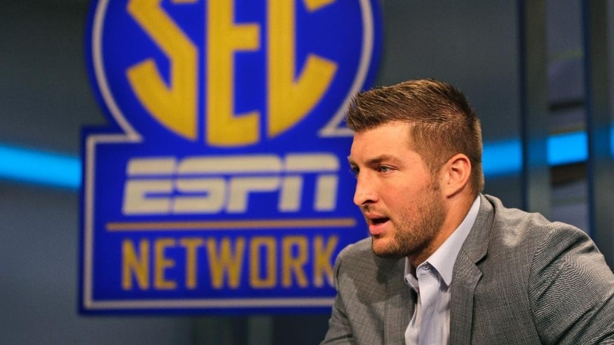 Tim Tebow answers a question during an interview on the set of ESPN's new SEC Network in Charlotte, N.C., Wednesday, Aug. 6, 2014. Tebow has a new job as a commentator for the SEC Network, but is still looking for work in the NFL as a quarterback. (AP Photo/Chuck Burton)