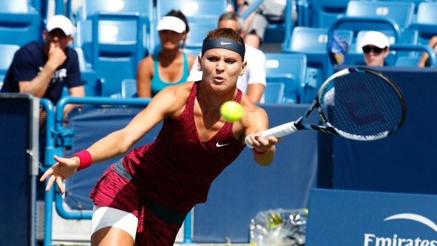 Lucie Safarova, from Czech Republic, returns to Venus Williams during a first round match at the Western & Southern Open tennis tournament, Tuesday, Aug. 12, 2014, in Mason, Ohio. (AP Photo/David Kohl)