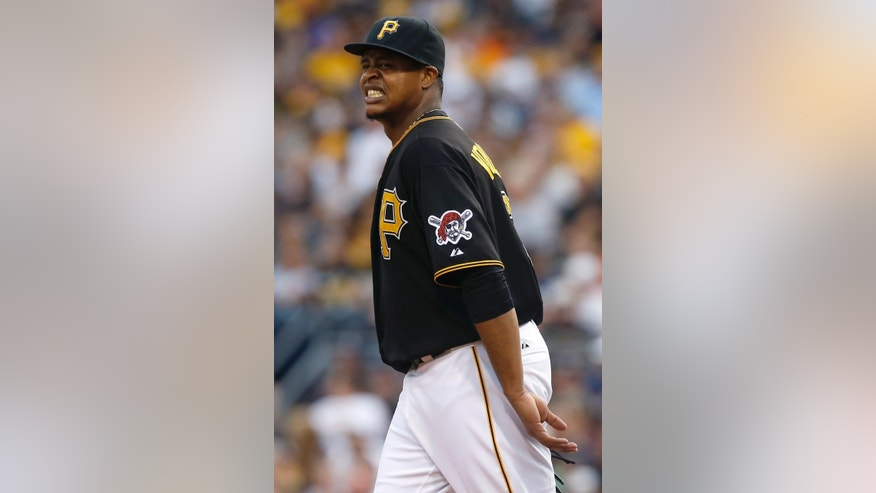 Pittsburgh Pirates starting pitcher Edinson Volquez grimaces after knocking down a line drive by Detroit Tigers' Victor Martinez and throwing it to home to force out Tigers' Ian Kinsler at the plate in the first inning of the baseball game on Tuesday, Aug. 12, 2014, in Pittsburgh. Martinez was safe at first and Volquez stayed in the game. (AP Photo/Keith Srakocic)