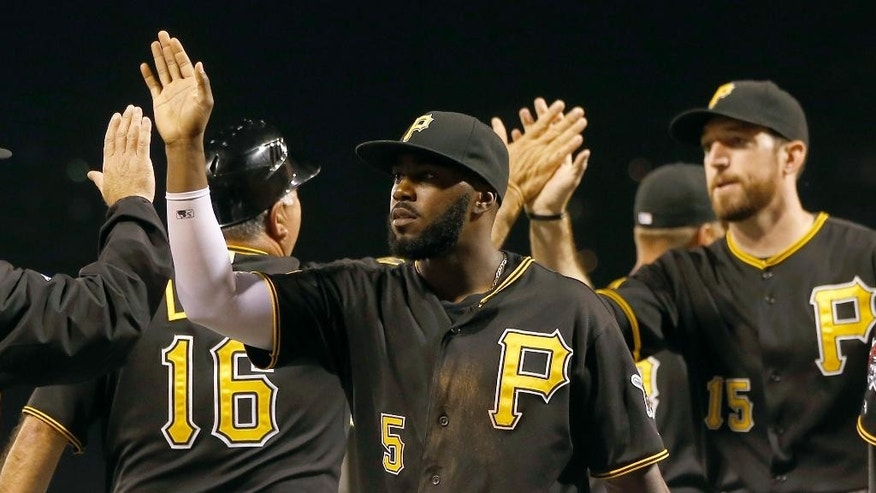 Pittsburgh Pirates' Josh Harrison (5) and Ike Davis celebrate with teammates after they defeated the Detroit Tigers in the baseball game on Tuesday, Aug. 12, 2014, in Pittsburgh. The Pirates won 4-2. (AP Photo/Keith Srakocic)