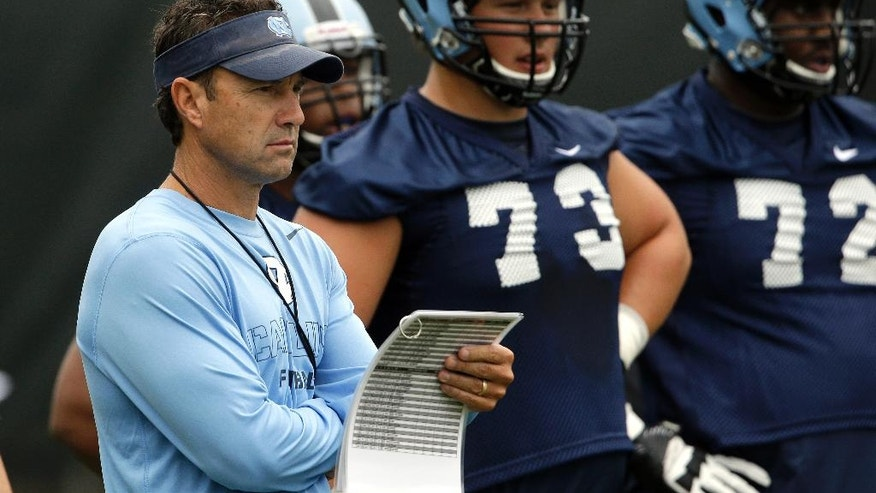 In this photo taken Friday, Aug. 1, 2014,  North Carolina coach Larry Fedora watches his team during an NCAA football practice in Chapel Hill, N.C. Brad Henson (73) and Kiaro Holts (72) look on at right. (AP Photo/Gerry Broome)