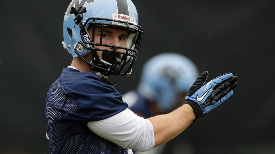 In this photo taken Friday, Aug. 1, 2014, North Carolina wide receiver Ryan Switzer signals a teammate during an NCAA football practice in Chapel Hill, N.C. (AP Photo/Gerry Broome)