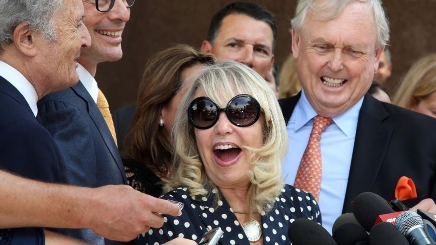FILE - In this July 28, 2014, file photo, with her attorney Pierce O'Donnell, right, Shelly Sterling, center, talks to reporters after a judge ruled in her favor and against her estranged husband, Los Angeles Clippers owner Donald Sterling, in his attempt to block the $2 billion sale of the NBA basketball team, outside Los Angeles Superior Court. Steve Ballmer is officially the new owner of the Clippers. The team says the sale closed Tuesday, Aug. 12, 2014,  after a California court confirmed the authority of Shelly Sterling, on behalf of the Sterling Family Trust, to sell the franchise. (AP Photo/Nick Ut, File)