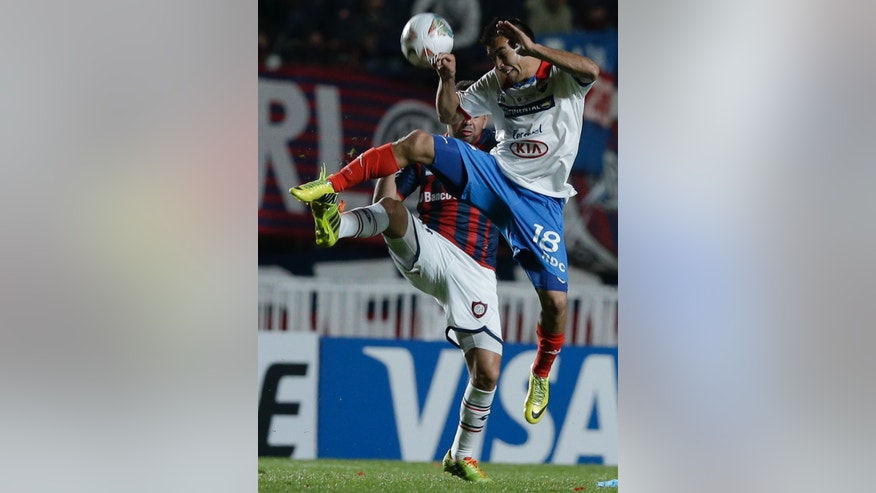Derlis Orue, right, of Paraguay's Nacional fights for the ball with Nestor Ortigoza of Argentina's San Lorenzo during the Copa Libertadores final soccer match in Buenos Aires, Argentina, Wednesday, Aug. 13, 2014. (AP Photo/Natacha Pisarenko)