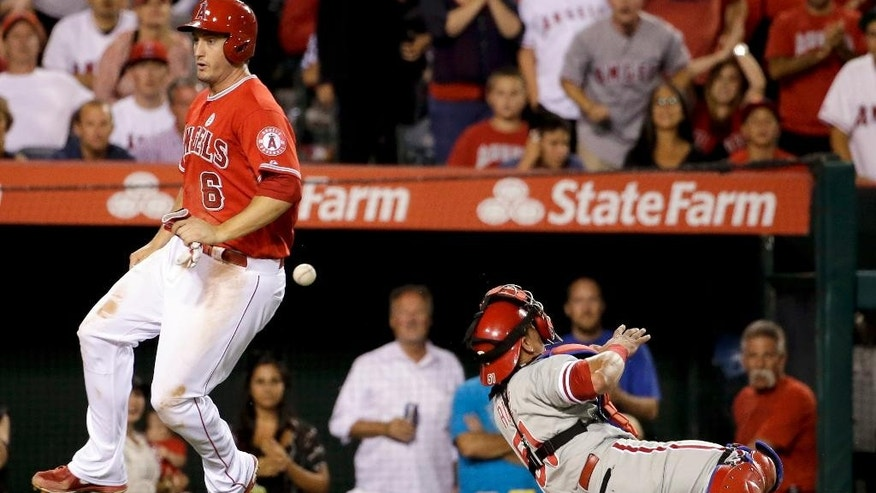 Los Angeles Angels' David Freese, left, scores past Philadelphia Phillies catcher Carlos Ruiz on a hit by Chris Iannetta during the sixth inning of a baseball game in Anaheim, Calif., Tuesday, Aug. 12, 2014. (AP Photo/Chris Carlson)