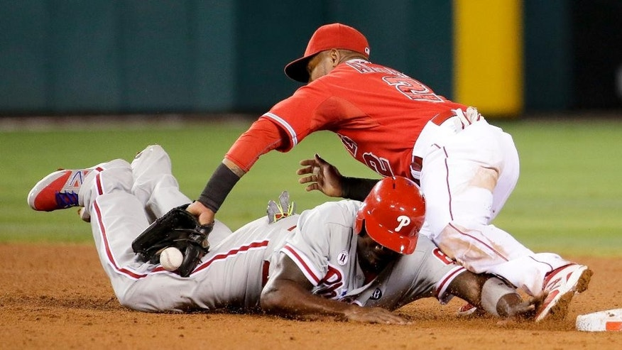 Philadelphia Phillies' Ryan Howard, bottom, dives safely back to second base after Los Angeles Angels shortstop Erick Aybar fails to catch the throw during the sixth inning of a baseball game in Anaheim, Calif., Tuesday, Aug. 12, 2014. (AP Photo/Chris Carlson)