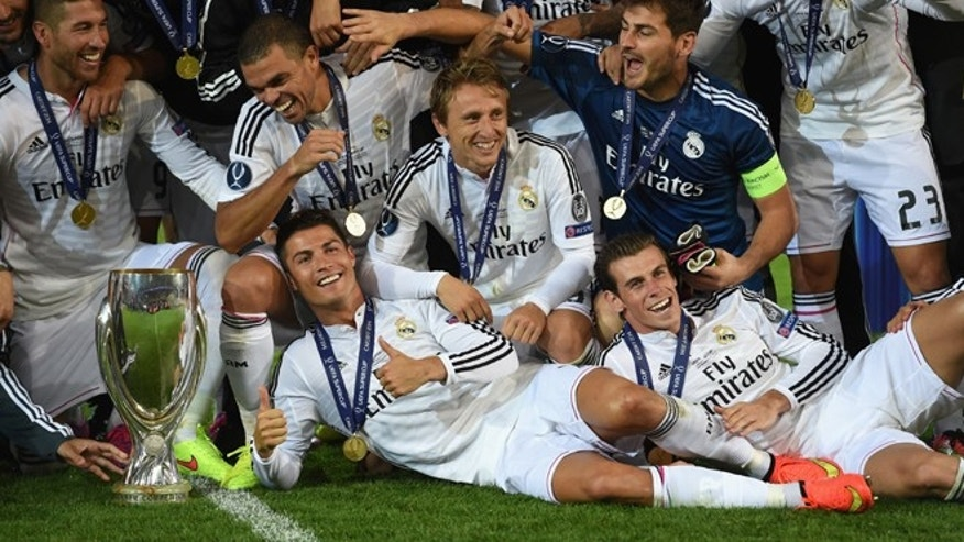 CARDIFF, WALES - AUGUST 12:  Real Madrid players Ronaldo (c) and Gareth Bale (r) celebrate with team mates and the trophy after the UEFA Super Cup match between Real Madrid and Sevilla FC  at Cardiff City Stadium on August 12, 2014 in Cardiff, Wales.  (Photo by Stu Forster/Getty Images)