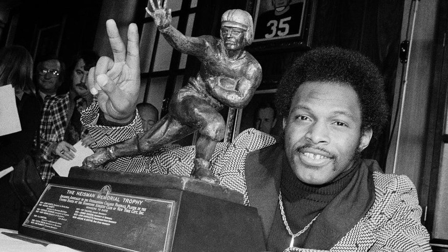 FILE - In this Dec. 2, 1975 file photo, Ohio State's running back Archie Griffin smiles and holds up two fingers as he poses with the 1975 Heisman Trophy in New York. Florida State quarterback Jameis Winston has the opportunity to accomplish what only one other player has achieved _ win consecutive Heisman trophies. Griffin won the award 1974 and 1975. He is shocked that he remains the lone repeat winner since the award's inception in 1935.   (AP Photo/File)