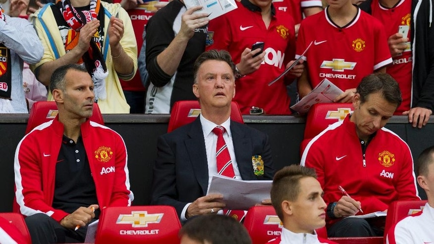 Manchester United's new manager Louis van Gaal, centre, takes his seat along side assistant manager Ryan Giggs, left, prior to his team's pre-season friendly soccer match,  against Valencia at Old Trafford Stadium, Manchester, England, Tuesday Aug. 12, 2014. (AP Photo/Jon Super)
