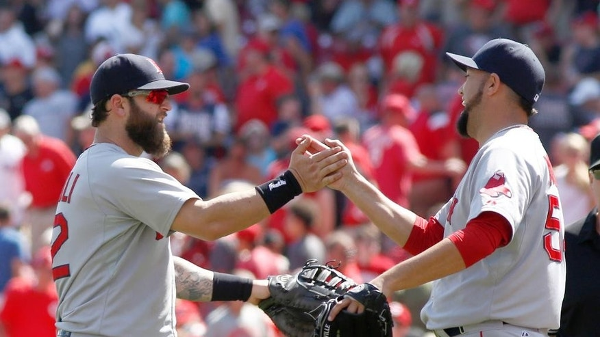 Boston Red Sox' Mike Napoli, left, and pitcher Edward Mujica congratulate each other after the Red Sox beat the Cincinnati Reds 5-4 in a baseball game, Wednesday, Aug. 13, 2014, in Cincinnati.  (AP Photo/David Kohl)