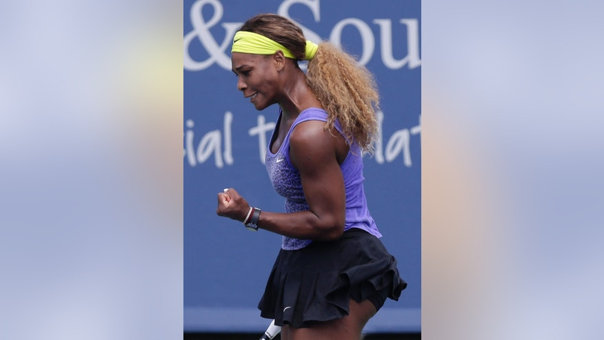 Serena Williams clinches her fist after hitting a shot against Samantha Stosur, from Australia, during a match at the Western & Southern Open tennis tournament, Wednesday, Aug. 13, 2014, in Mason, Ohio. (AP Photo/Al Behrman)