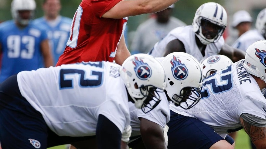 FILE - In this July 27, 2014, file photo, Tennessee Titans quarterback Jake Locker calls a play during NFL football training camp in Nashville, Tenn. The majority of teams pay their starting quarterbacks just a fraction of the base salaries of the Peyton Mannings, Tom Brady and Jay Cutler, who makes $17.5 million this season. The Titans declined to pick up the 2015 option on Locker because he has missed 14 of 32 games since being named the starter, and he's costing a mere $2 million in salary this season. (AP Photo/Mark Humphrey, File)