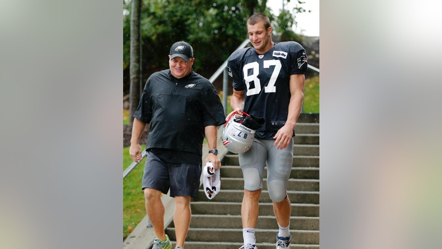 Philadelphia Eagles head coach Chip Kelly and New England Patriots tight end Rob Gronkowski (87) chat as they leave a joint NFL football training camp practice in Foxborough, Mass., Wednesday, Aug. 13, 2014. (AP Photo/Elise Amendola)