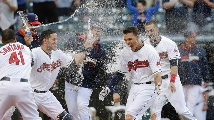 Cleveland Indians' Zack Walters , right, is mobbed by teammates after hitting a game-winning solo home run off Arizona Diamondbacks relief pitcher Randall Delgado in the ninth inning of the first baseball game of a doubleheader, Wednesday, Aug. 13, 2014, in Cleveland. The Indians defeated the Diamondbacks 3-2. (AP Photo/Tony Dejak)