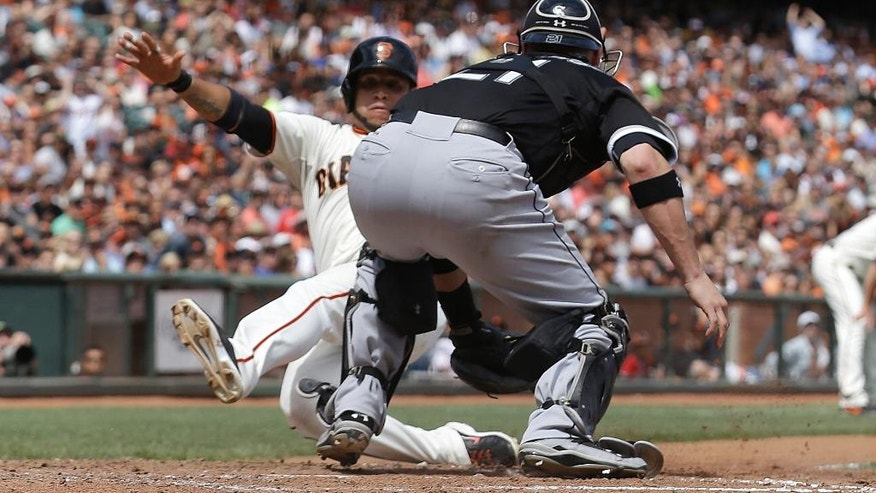 Chicago White Sox catcher Tyler Flowers, right, reaches to tag San Francisco Giants' Gregor Blanco, who was originally ruled out at home but then ruled safe after review, during the seventh inning of a baseball game in San Francisco, Wednesday, Aug. 13, 2014. (AP Photo/Jeff Chiu)