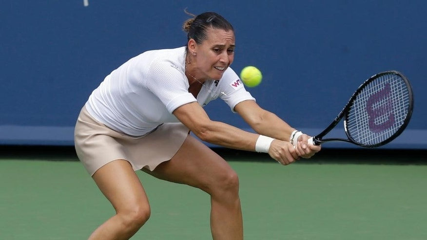 Flavia Pennetta, from Italy, returns a serve against Serena Williams during a match at the Western & Southern Open tennis tournament, Thursday, Aug. 14, 2014, in Mason, Ohio. (AP Photo/Al Behrman)