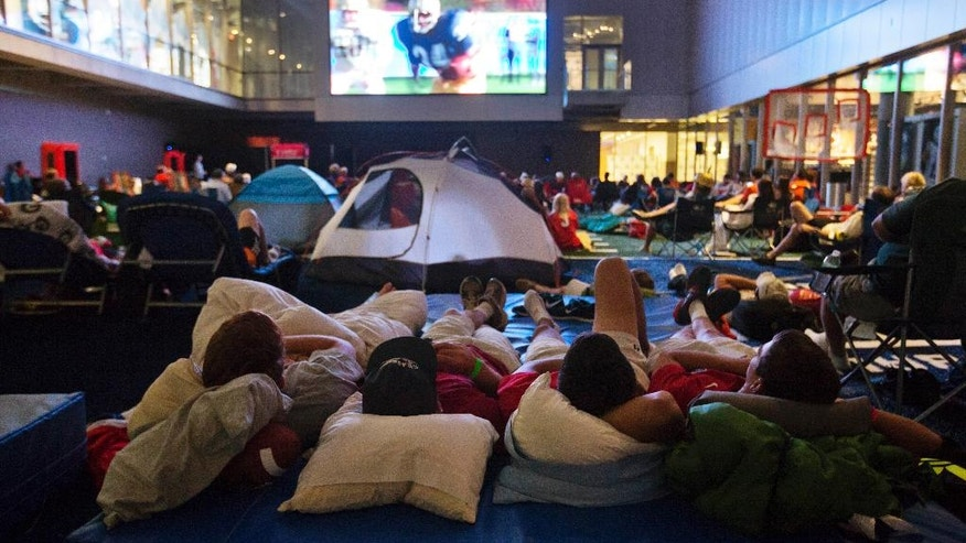 "From left, Danny Mason, Walker Tuten, Nick Toomey and Matt Filer, watch the movie ""Rudy"" during a sleepover in the College Football Hall of Fame, Wednesday, Aug. 13, 2014, in Atlanta. The crowd fell asleep to the playing of college football themed movies such as ""Rudy"" and ""We are Marshall"" on the jumbotron.  (AP Photo/David Goldman)"