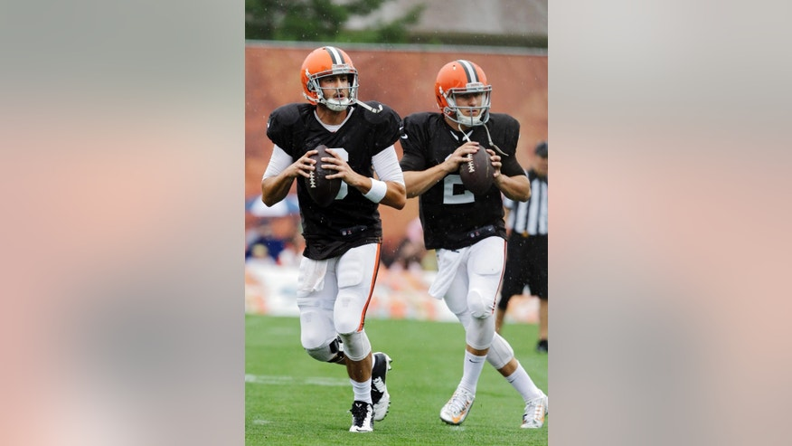 Cleveland Browns quarterbacks Brian Hoyer, left, and Johnny Manziel drop back to pass during practice at NFL football training camp in Berea, Ohio on Monday, Aug. 11, 2014. (AP Photo/Mark Duncan)
