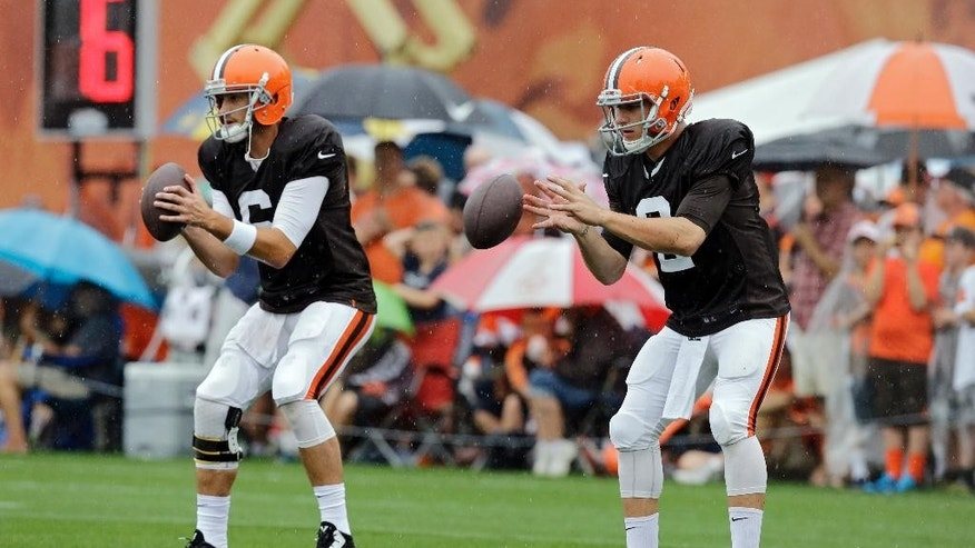Cleveland Browns quarterbacks Brian Hoyer, left, and Johnny Manziel take snaps during practice at NFL football training camp in Berea, Ohio on Monday, Aug. 11, 2014. (AP Photo/Mark Duncan)