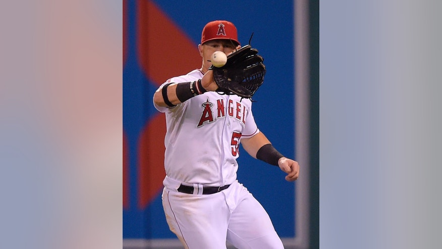 Los Angeles Angels right fielder Kole Calhoun fields a ball hit for an RBI single by Philadelphia Phillies' Jimmy Rollins during the fourth inning of a baseball game, Wednesday, Aug. 13, 2014, in Anaheim, Calif. (AP Photo/Mark J. Terrill)