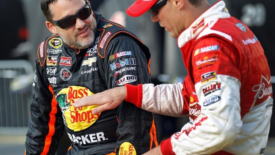 FILE - In this May 22, 2014, file photo, Tony Stewart, left, talks with Kevin Harvick before qualifying for a NASCAR Sprint Cup series auto race at Charlotte Motor Speedway in Concord, N.C. Stewart is skipping a second straight Sprint Cup race, and it is not clear when the NASCAR star might return after he struck and killed a driver at a dirt-track race in New York last weekend. (AP Photo/Terry Renna, File)