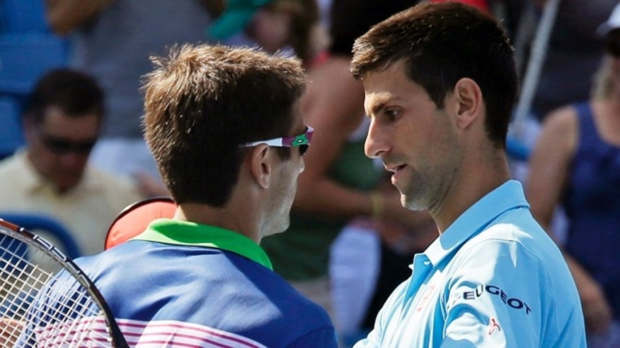 Novak Djokovic, right, congratulates Tommy Robredo on Thursday, Aug. 14, 2014, in Mason, Ohio.