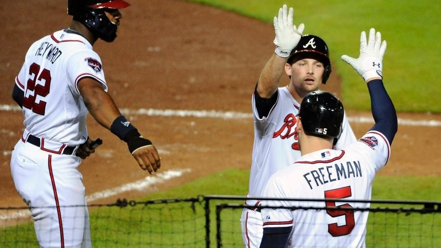 Atlanta Braves' Phil Gosselin, center, is greeted by Freddie Freeman and Jason Heyward after Gosselin's first major league home run which scores Heyward during the sixth inning of a baseball game against the Oakland Athletics Friday, Aug. 15, 2014, in Atlanta. (AP Photo/David Tulis)
